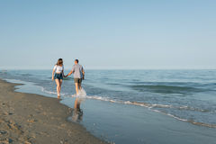 Das Mädchen hält den Kerl durch eine Hand gehend zum Meer Stockfotografie