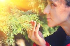 Das Mädchen hält einen Baumast in ihrer Hand und genießt den Geruch lizenzfreies stockfoto