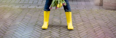 Das Mädchen hält einen Blumenstrauß von frischen Frühlingstulpen Straße der alten Stadt Gelbe Gummimatten Freier Platz für Text lizenzfreies stockfoto