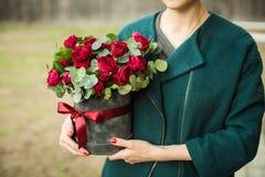 Das Mädchen hält einen Blumenstrauß von roten Rosen in ihren Händen lizenzfreie stockbilder