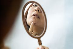 Das Mädchen hält einen kleinen Spiegel vor ihr und überprüft die Haut auf ihrem Gesicht mit Akne Sorgfalt für Problemhaut lizenzfreies stockbild