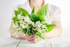 Das Mädchen hält einen schönen Blumenstrauß von Maiglöckchen in ihren Händen Lizenzfreie Stockfotografie