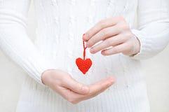 Das Mädchen hält in ihrer Hand ein rotes Herz, das von der Wolle gestrickt wird lizenzfreie stockbilder