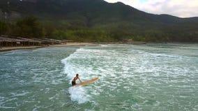 Das Mädchen hält Surfbrett auf Wasser gehend in schäumende Wellen stock video