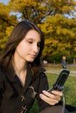 Das Mädchen hält Telefon an Lizenzfreies Stockfoto