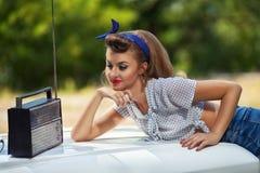 Das Mädchen hört antiken Radio auf der Haube des Autos auf grünem Hintergrund Stockfotos