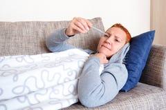 Das Mädchen hat die Grippe Lügen im Bett, das den Thermometer betrachtet Falsche Nachrichten Hohe Temperatur Kälte und Grippe Das stockfotos
