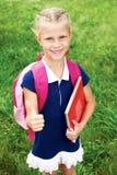 Das Mädchen hat eine Schultasche und Bücher Mädchen zeigt Geste O Stockfotografie