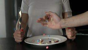 Das Mädchen hat Pillen von der Platte mit einem Messer und einer Gabel Das Konzept des verlierenden Gewichts mit Pillen oder rege stock video footage