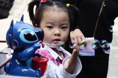 das Mädchen hat Spaß mit Spielzeug im Disney-Land Lizenzfreie Stockfotografie