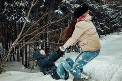 Das Mädchen hebt ihren Freund aus dem Schnee heraus an stockfotografie