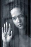 Das Mädchen hinter Glas Stockfoto