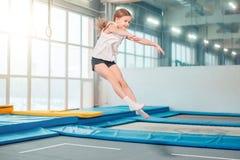 Das Mädchen hoch springend in gestreifte Strumpfhosen auf Trampoline stockfotografie