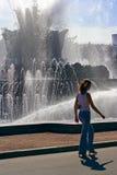Das Mädchen, ihr Schatten und ein Brunnen Lizenzfreies Stockfoto