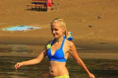 Das Mädchen im Badeanzug mit einem Lächeln geht in das Wasser Lizenzfreies Stockfoto