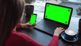 Das Mädchen im Café arbeitet mit Geräten mit grünen Schirmen stock video