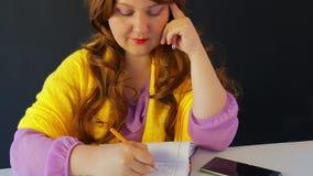 Das Mädchen im Café am Tisch schreibt in das Tagebuch stock footage
