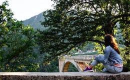 Das Mädchen im Denim kleidet das Sitzen am Rand des Zauns und betrachtet das Brücke Ä  urÄ ` eviÄ ‡ a Stockfotografie