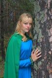 Das Mädchen im grünen Regenmantel, nestled auf einer Kiefer Lizenzfreie Stockfotografie