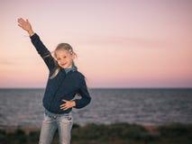 Das Mädchen im Gras auf der Seeseite am Abend Stockfoto