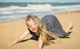 Das Mädchen im grauen Kleid auf dem Sand durch den Ozean Lizenzfreies Stockfoto