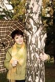 Das Mädchen im Herbstpark mit einem Regenschirm. lizenzfreie stockfotografie