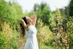 Das Mädchen im Holz in der Sonne strahlt Stockfotos