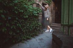 Das Mädchen im Hut öffnet einen Briefkasten mit Blättern am Hintergrund des alten Hauses stockfotografie