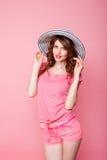 Das Mädchen im Hut auf einem rosa Hintergrund Pinup stockfotografie
