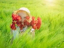 Das Mädchen im Hut bedeckt ihr Gesicht mit einem Blumenstrauß von Mohnblumen auf einem Gebiet des Grünroggens Lizenzfreies Stockfoto