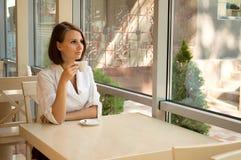 Das Mädchen im Kaffee hinter einem Tasse Kaffee Lizenzfreie Stockbilder