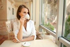 Das Mädchen im Kaffee trinkt Kaffee Stockfoto