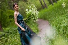 Das Mädchen im Kleid erfasst Blumen Stockbilder
