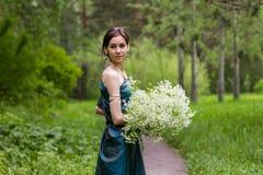 Das Mädchen im Kleid erfasst Blumen Lizenzfreie Stockfotos