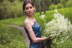 Das Mädchen im Kleid erfasst Blumen Lizenzfreies Stockfoto