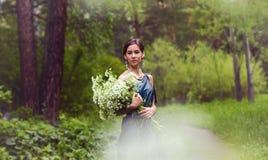 Das Mädchen im Kleid erfasst Blumen Stockbild