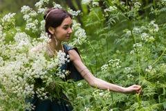 Das Mädchen im Kleid erfasst Blumen Stockfotos