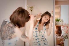 Das Mädchen im Kleid schaut im Spiegel stockbild