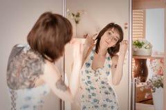 Das Mädchen im Kleid schaut im Spiegel stockbilder