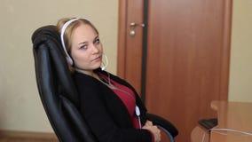 Das Mädchen im Kopfhörer sitzt auf einem Stuhl nahe dem Computer stock footage