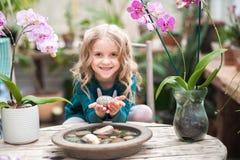Das Mädchen im Orchideengewächshaus wird mit Blumen und Steinen gespielt Mädchen mit blühenden Orchideen hält Steine lizenzfreie stockfotos