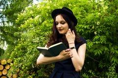 Das Mädchen im Park ein Buch lesend Stockfotos