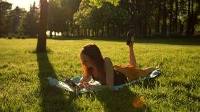 Das Mädchen, das im Park unter den Bäumen sitzt und benutzen das Internet auf Tablette stock video footage