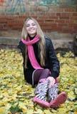 Das Mädchen im rosafarbenen Schal und in den Matten Stockfotografie