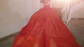 Das Mädchen im roten Kleid, welches oben die Treppe laufen lässt stock footage