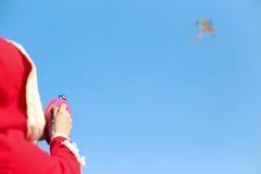 Das Mädchen im roten Mantel hält an das Seil der Fliegenschlange, die im Himmel ansteigt Stockfotografie
