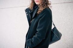 Das Mädchen im schwarzen Mantel und mit dem Geldbeutel auf ihrer Schulter gehend tun lizenzfreie stockfotos