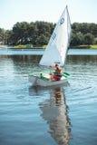 Das Mädchen im Segelboot auf dem See Lizenzfreies Stockbild