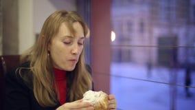 Das Mädchen im trinkenden Tee und im Essen des Cafés eines Brötchens stock video