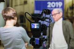 Das Mädchen interviewt den Mann Videodreh im Innenraum Lcd-Anzeige auf dem Kamerarecorder lizenzfreies stockbild